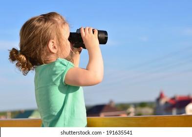 Cute girl looking through binoculars.