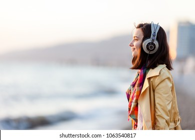 A cute girl looks at the sunset in bright clothes and listens to music in big headphones