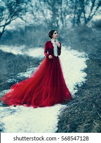 Cute girl in luxurious red dress. Fashionable toning
