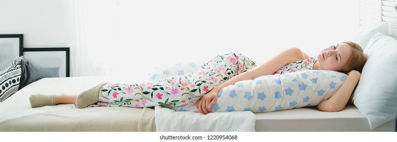 Cute girl lying in bed with body pillow. Concept of comfortable sleep