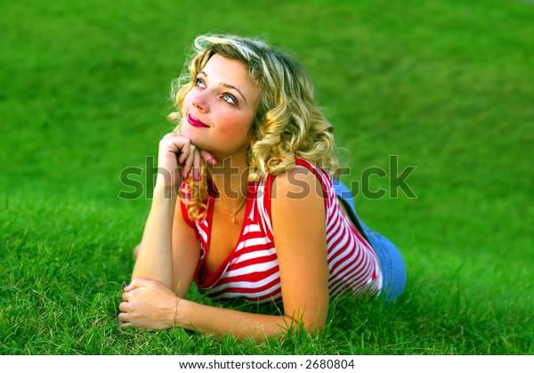 Cute girl lying on the green grass