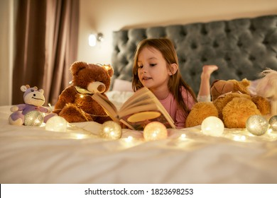 A cute girl is lying on her stomack in a huge bed barefoot reading a book, having her teddybears and dreamy garlands around the bed in a big bedroom at home. Happy childhood