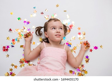 A cute girl is lying on a white background in confetti. A blonde girl with ponytails in a pink dress. Children's holiday. On white background with copy space.