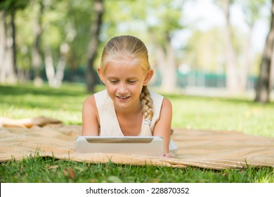 Cute girl lying in park and using tablet pc