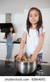 Cute girl mixing dough in kitchen with mother in background