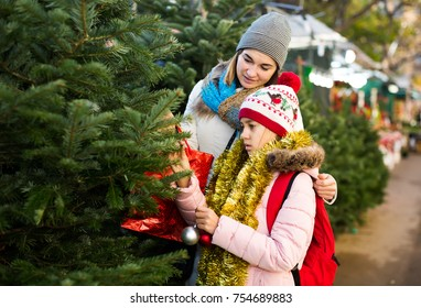 Cute girl with mom choosing New Year's tree outdoors