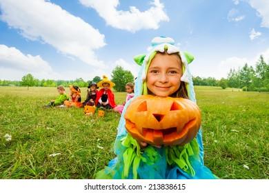 Cute girl in monster costume holds pumpkin