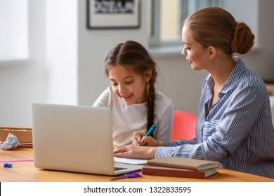 Cute Girl mit Mutter, die zu Hause Hausaufgaben macht