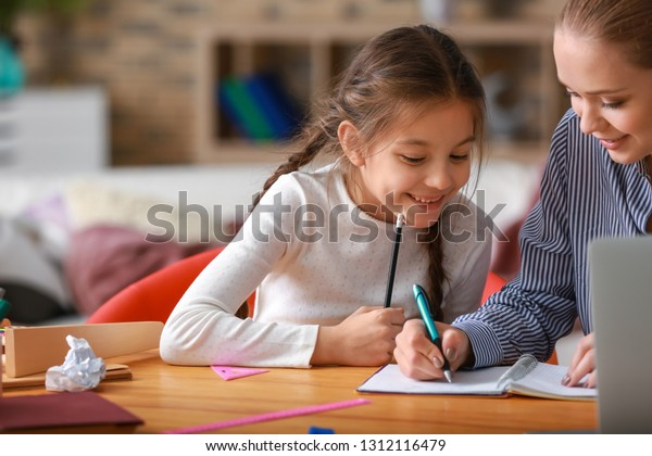 Cute girl with mother doing homework at home