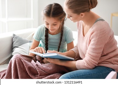 Cute girl with mother reading book at home