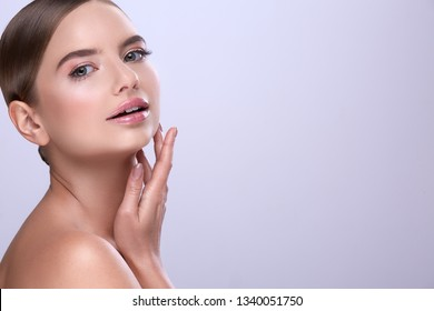 Cute girl with naked shoulders, fixed hair and nude make up posing at white background, make up tutorial, close up portrait.