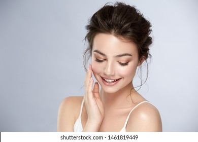 cute girl with natural make-up smiling and looking down, young and healthy woman facial care, cosmetology and dental concept