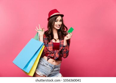 Cute girl  with nude make up and curly hair posing at pink studio background with shopping bags, shopping concept, discounts, black Friday.