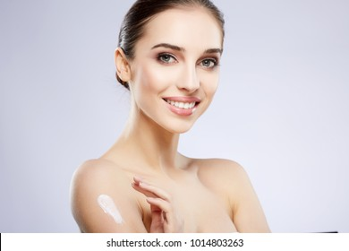 Cute girl with nude make up posing at grey studio background, beauty photo concept, perfect skin, using skin cream and smiling.