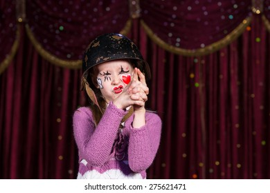 Cute girl with old helmet and with a red heart painted on face pretending to have a gun in a conceptual play about war, love and innocence