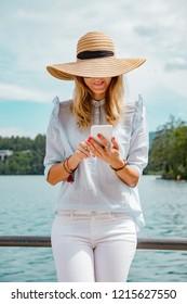 Cute girl on lake using smartphone.