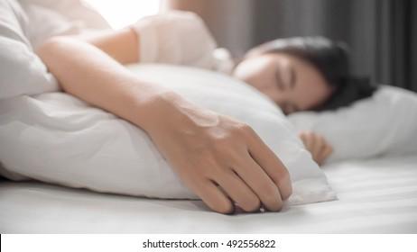 Menina bonita em uma cama branca macia. Ela dorme e relaxa.