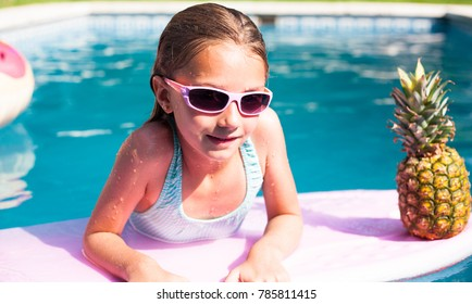 Cute girl on the surf board in a pool with a pineapple