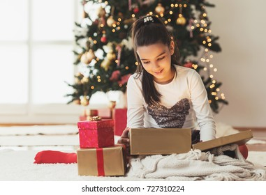 Cute girl opening a present on a Christmas morning