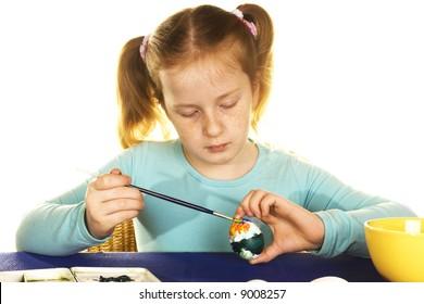 cute girl is painting easter eggs