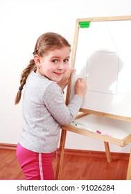 Cute girl painting on chalkboard