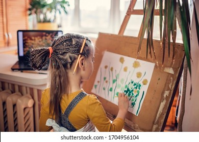 A cute girl with pallet, easel and brush drawing sunny flowers imaged in the screen of laptop as if she is on plein air, self-isolation and lifestyle in quarantine time, online workshop