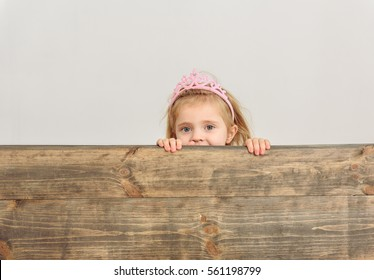 Cute girl peeping over wooden border
