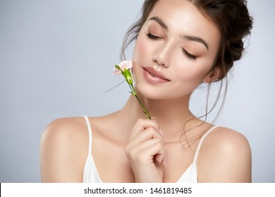 cute girl with perfect skin and white flower near face closed eyes, natural facial care with brunette, clean skin and glossy lips