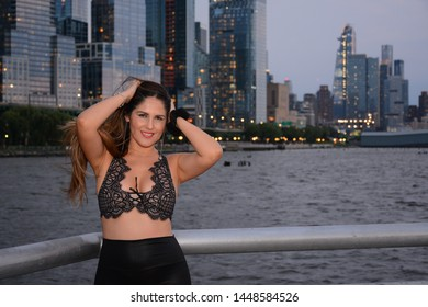 Cute girl from Peru on the pier with Manhattan view at night, New York, USA