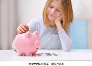 Cute girl with piggy bank and coins at home