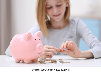 Cute girl with piggy bank and coins at home, closeup