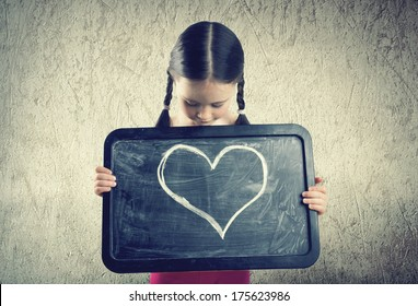 Cute girl with pigtails holds a board with a painted heart