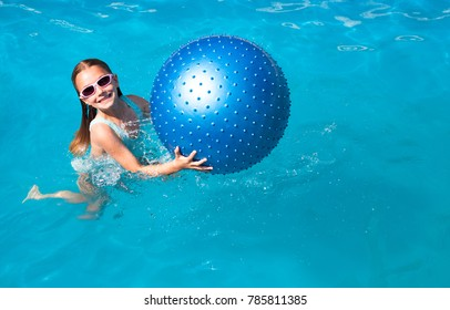 Cute girl playing with a blue ball in a swimming pool