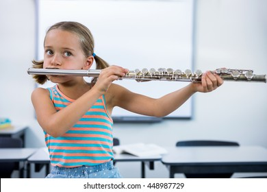 Cute girl playing flute in classroom