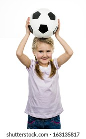 Cute girl playing football, happy child, young female goalkeeper enjoying sport game, holding ball, isolated portrait of a preteen smiling and having fun, kids activities, little footballer