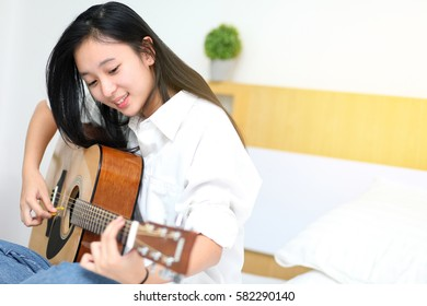 Cute girl playing guitar on the bedroom.