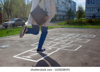 Cute girl playing hopscotch outside