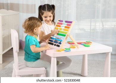 Cute girl playing with little sister at home