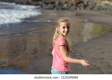 cute girl is playing on sandy beach