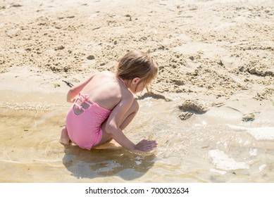 Cute girl playing in the sand on the beach. Back view