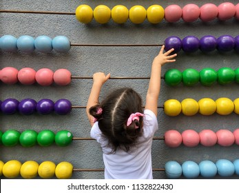 A cute girl playing with wooden abacus. Educational concept for kids. Learing to count. Math for children.