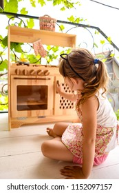 A cute girl playing with the wooden toy kitchen