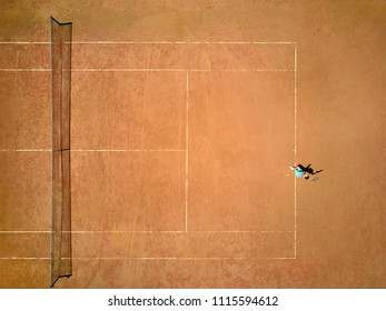 Cute girl plays tennis on the court outdoors. She prepares to beat on a ball. Woman wears a light blue sportswear with white sneakers. Top view horizontal photo.