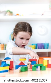 cute girl plays with toy building blocks at kindergarten