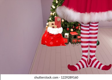 cute girl with pointed elven feet wearing elf legging standing in a room with a christmas tree and santa claus bag full of presents on the background