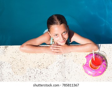 Cute girl in a pool with a drink