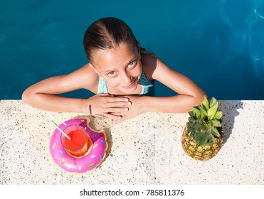Cute girl in a pool with a drink and pineapple