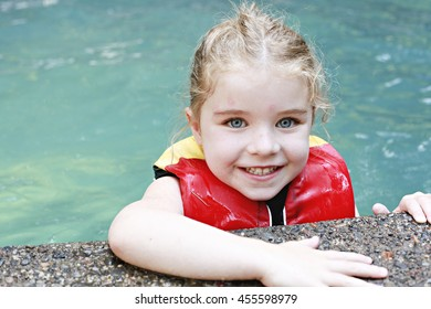 A cute girl in the pool with her life jacket