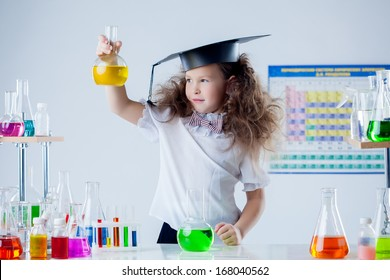 Cute girl posing with colorful test-tubes in lab