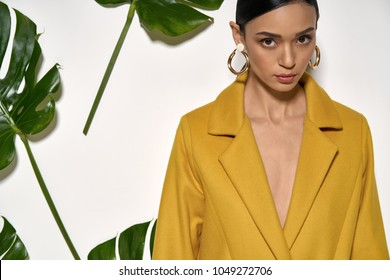Cute girl is posing in a studio on a background of a white wall with big green leaves. She wears a mustard coat and looks into a camera. Closeup. Horizontal.
